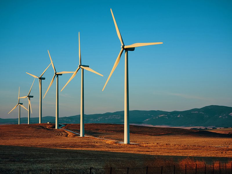 Six electric wind turbines in a row located in grassy field with mountains in background