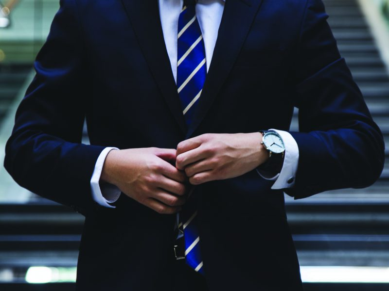 Lawyer fastening the top button on a dark blue tailored suit