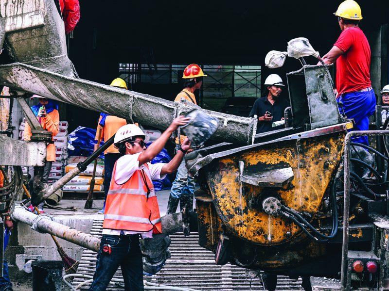 Contruction worker pouring wet concrete into construction equipment
