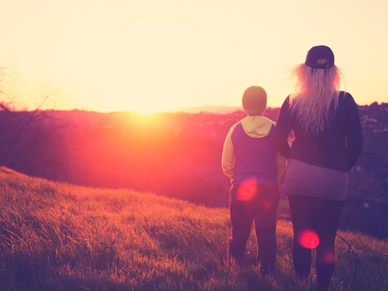Mother and son enjoying a chilly sunset in a grassy meadow