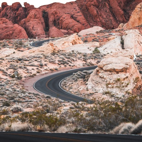 Difficult winding two-way road leading to beautiful orange-like desert mountain destination